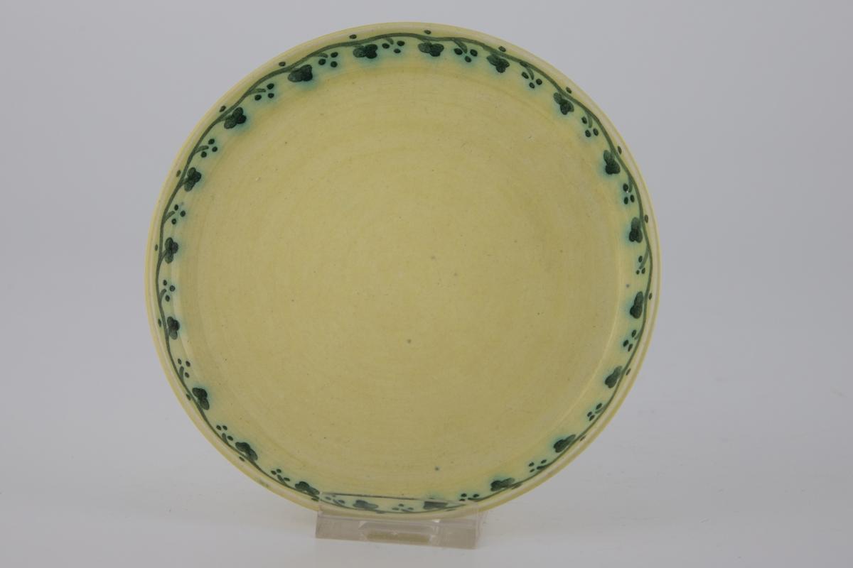 Kaffekopp med tilhørende skål i gulfarget glasur, dekorert med emaljemaling. Dekoren er mørkegrønn, og er utformet som et stilisert planteornament som slynger seg langs fatets og koppens kant.