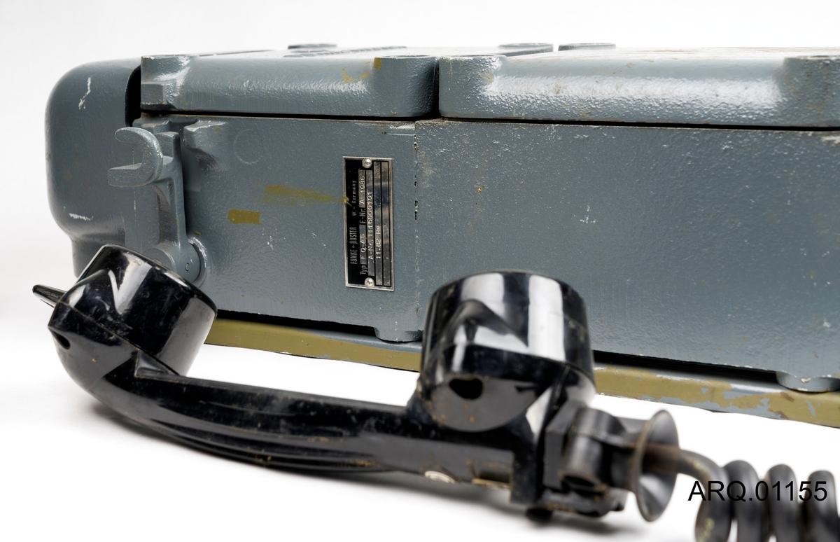 """En tyskprodusert """"Gruvetelefon"""", produsert av selskapet; FUNKE+HUSTER. Har oppheng i form av skinner på baksiden av telefonkassen. Telefonene er en rektangulær kasse med kabeluttak på undersiden, samt støpsel til telefonrøret. Telefonrøret er av bakelitt. Telfonen (kassen) er jern/Stål."""