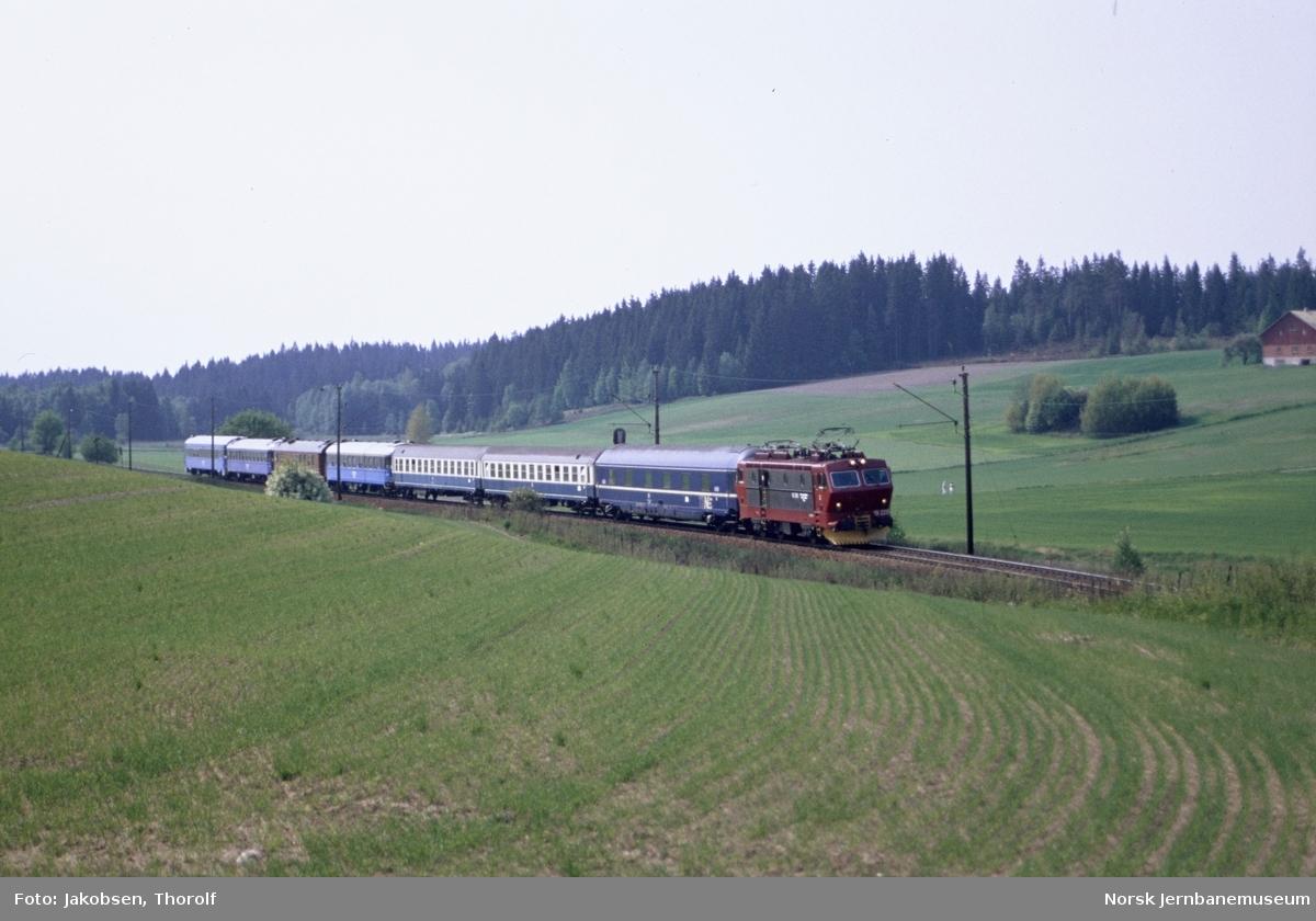 Elektrisk lokomotiv El 16 2215 med persontog fra Hamburg til Oslo S, tog 280, ved km 29 mellom Ås og Holstad stasjoner på Østfoldbanen
