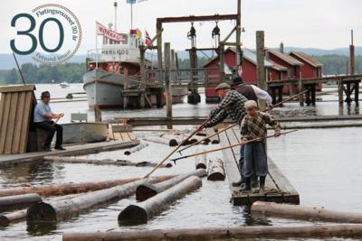 Foto av personer med fløterhaker som håndterer tømmer i elva. Fetsund lensers jubileumslogo i øvre venstre hjørne.. Foto/Photo