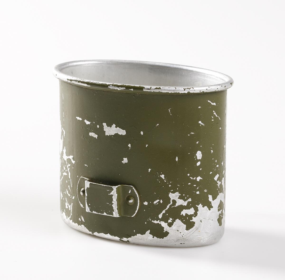 """Tyska arméns, M1931, vattenflaska, (Feldflasche) i aluminium med ett impregnerat och pressat träfiberlaminerat hölje och svart bakelitskruvkork. Komplett med gröna kakiremmar med stålbeslag och en svart läderrem runt flaskans hals. Flaskan har 0,8 liters kapacitet. Det är präglat på baksidan av träskyddet av plast """"D.R.G.M. / H.R.E.41 / D.R.P. angm."""". (Deutsche Reichs Gebrauchs Muster/Heinrich Ritter, Esslingen, 1941/Deutsches Reichs Patent angemeldet). Remmarna har ett fjäderbelastat stållås för att fästa flaskan på bältet, vilket är stämplad """"PATENT RITTER"""". De stålförsedda remspetsarna har en märkning inom cirkel """"SHB"""". Metalljusteringsspännet på selen är målat i DAK-grönt och märkt """"DRP. ang. HRE 42"""". Ett litet cirkulärt varumärke finns präglat på toppen av bakelitlocket som innehåller """"7M"""" och bokstaven """"S"""". Lockets insida har en röd gummitätning. Flaskan är avsedd att användas i varma områden som Südfront (Sydfront), die Tropen (tropiska områden) eller vid DAK (Deutsche Afrika Korps). Fältflaskan gick ofta under namnet """"kokosnöten"""" (kokonuss) på grund av dess utseende. Matkärlet i aluminium är har en grönmålad utsida och insidan är helt metallren, men skall vara med röd emalj på insidan. Koppen är märkt mellan de båda greppbyglarna med """"HRE43"""" (Heinrich Ritter 1943)."""
