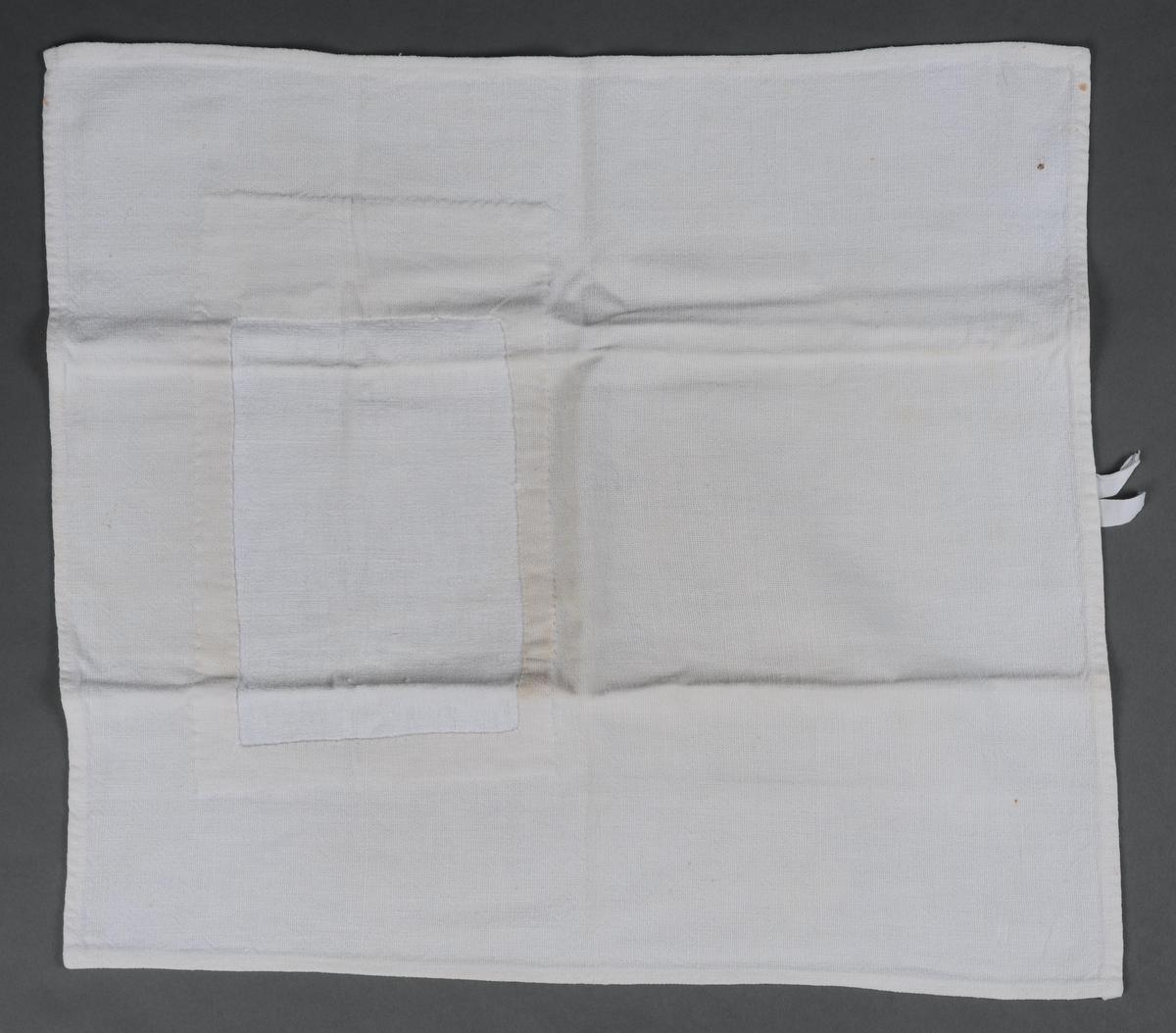Håndduk hvor alle 4 sider er kantet inn og sydd til med maskin. Hempe av bomullsbånd er sydd på med maskin midt på den ene kortsidene. Håndduken er bødt.