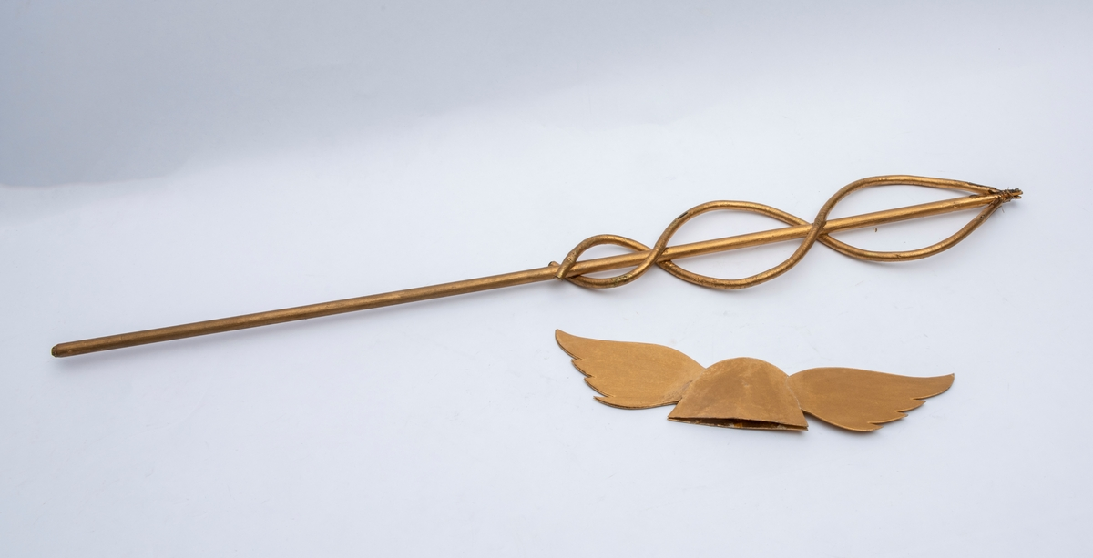 Forgylt. Laget av flettet kvist/bambus med en hatteformet del i papp til overstykke. Denne har muligens vært limt på. Den er nå løs.
