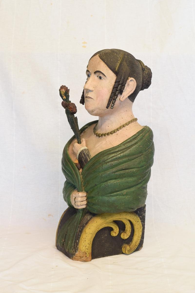 Portrettbyste av kvinnehode. Skulle brukes som gallionsfigurer men kan og ha vært brukt som dekorasjon i et hus. Sortmalt hår med hengekrøller ved ørene og grønt sjal. Holder et sortmalt blad i hånden.