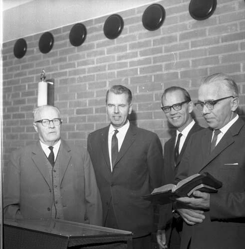 Fyra män i kostym står uppradade runt ett talarbord. Mannen till höger, Robert Svensson, håller två böcker i handen, eventuellt en bibel och en psalmbok. Olof Nilsson står intill honom.