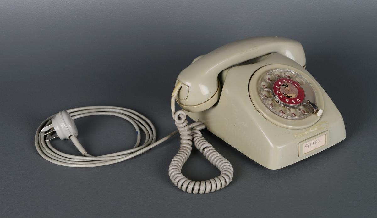"""En grå bordtelefon med rør. Står på fire gummiknotter og har plastdekkede ledninger. Blank dreieskive over røde tall. En mindre tallskive på selve dreieskiven i rødt med hvite tall. Det er et nesten helt avrevet klistremerke hvor det har stått telefonnummer til blant annet taxi. Et lite papirskilt på fremsiden med telefonnummeret skrevet for hånd. Undersiden er av messing, og har en justeringsknapp som kan stilles fra min til max. Merket med """"TELEVERKET"""" og en stjerne med lyn rundt."""