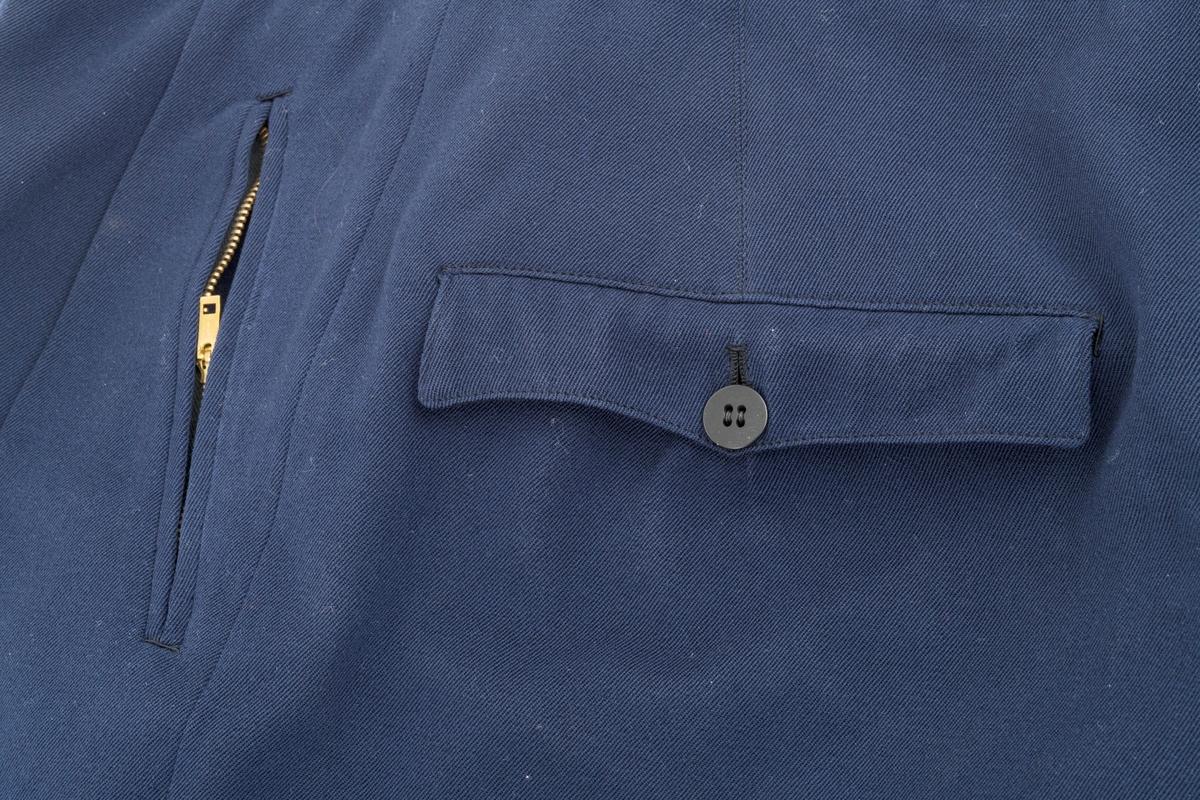 Strekkbukse til skidress i mørkeblå gabardin. Buksa har strikk for å ha under foten. To lommer ved hoftehøyde som lukkes igjen med glidelås. To lommer bak som lukkes igjen med knapper. Buksesmekken lukkes igjen med knapper. Bukselinningen er foret med bomullsstoff. Her er det to knapper foran og to bak til bruk av bukseseler. Buksa har også beltestropper.