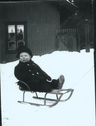 Wilhelm Fredrik Rydgren sitter på kjelke i snøen på gårdspla