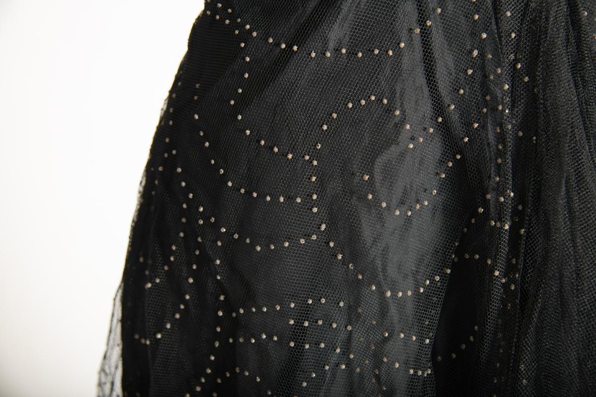 Selskapskjole med stropper, den ene festet med sikkerhetsnål. Stramt liv med spiler, vidt skjørt. Sydd av sort, glatt stoff, utenpå dette et nettingaktig stoff med små paljetter i bølgemønster. Glidelås i den ene siden.