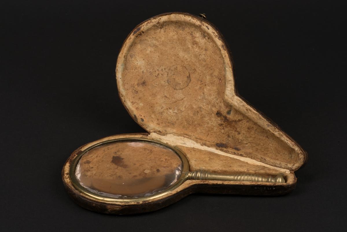 Förstoringsglas med runt glas, ram och handtag av mässing. Fodral av läder.