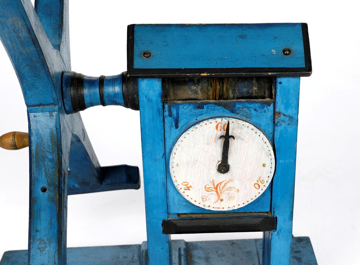 Blåmalt hespetre med telleapparat (basmehjul), tallskive og viser. Malt med svarte, hvite og oransje detaljer. Hjulet har fire armer. Ene armen kan bøyes utover.