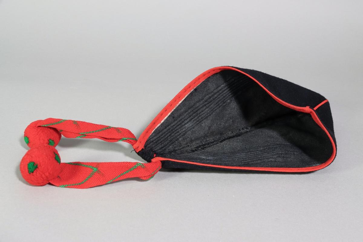 Hätta sk. gråhätta av svart yllekypert. Trekantig form av två stycken sammanfogade med en nacksöm med röd passepoal och kantad med rött ullband. Hättan är nedtill hopveckad med ett flätat band av rött ullgarn med grönt viggmönster. Bandet är trätt genom hål i tyget, som även ordnar vecken på sidorna, och avslutas med en rund röd ullboll med gröna prickar i varje ände. Bandändarna hänger ner i nacken och där finns också mitt bak en ögla av ett smalt rött ullband. Längs kantens insida är en smal remsa av ett mönstrat bomullstyg påsytt innanför det röda ullbandet. Maskin och handsömnad. Insidan av hättan är bestruken med någon form av stärkelse eller lim.