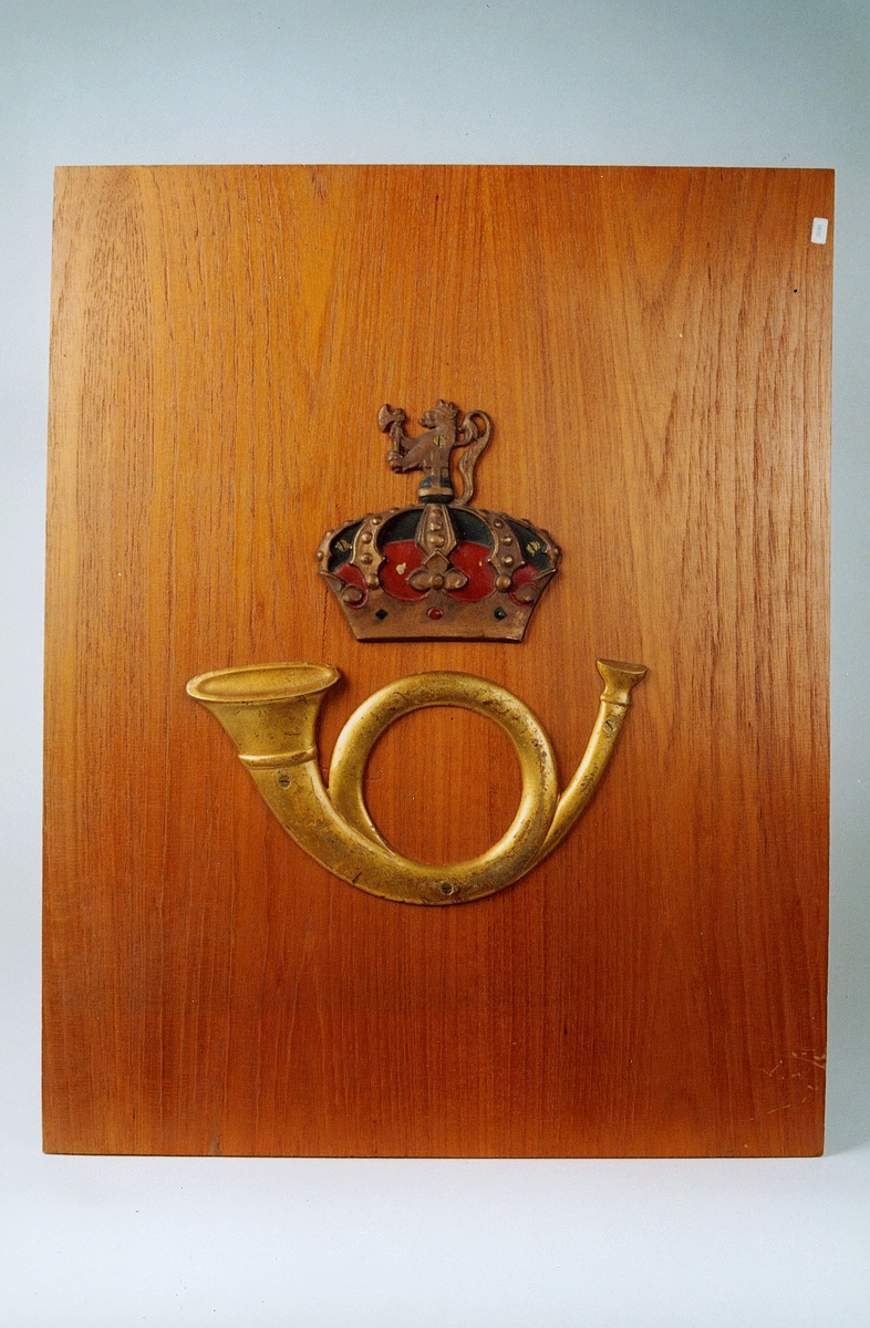 Postmuseet, gjenstander, skilt, postskilt, posthorn og krone med riksløve (postlogo) montert/skrudd fast på en treplate.