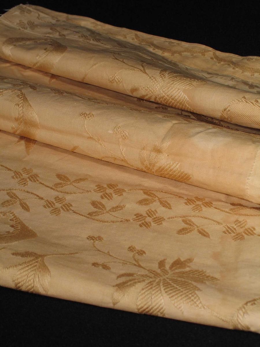 Gardinrest i ecrufarget jacquardvevet bomullstøy. Mønster: skiftevis brede og smale vertikale blomsterranker med sløyfebånd.