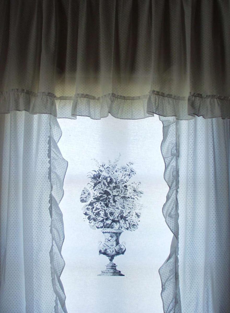 Et gardinfag med kappe sydd i hvitt gjennomsiktig bomullsstoff med flossete prikker.