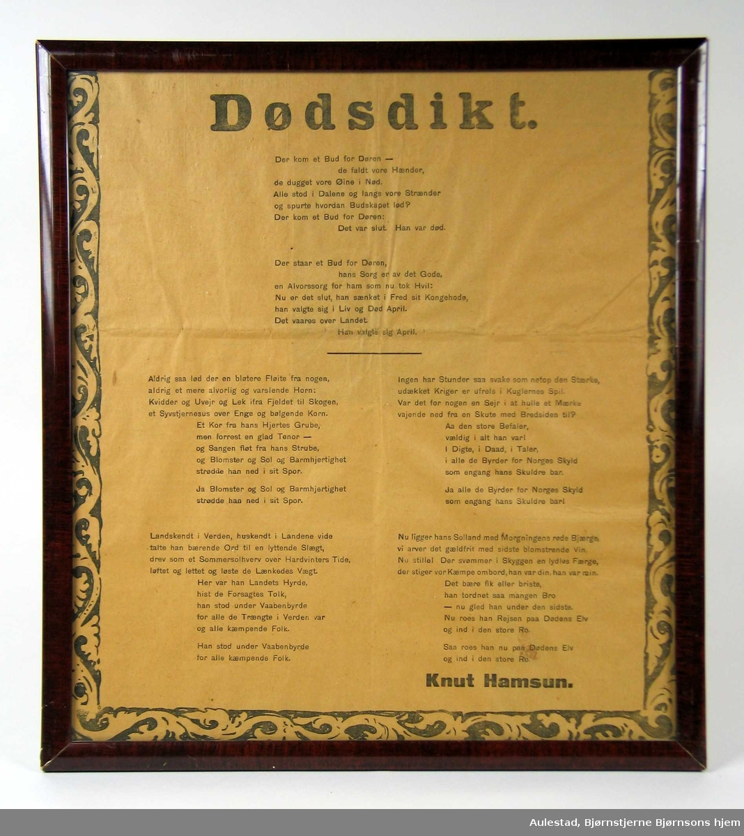 Dikt innrammet i brun lakkert treramme. Det er en akantusbord rundt diktet. Trykte bokstaver.