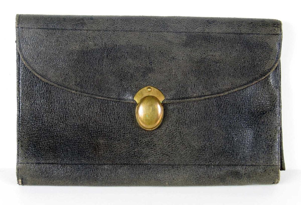 Seddelbok i svart skinn med gyllen skyvelås i metall. Lommeboken har to lommer og har lilla fôr. Bånd til notisbok.