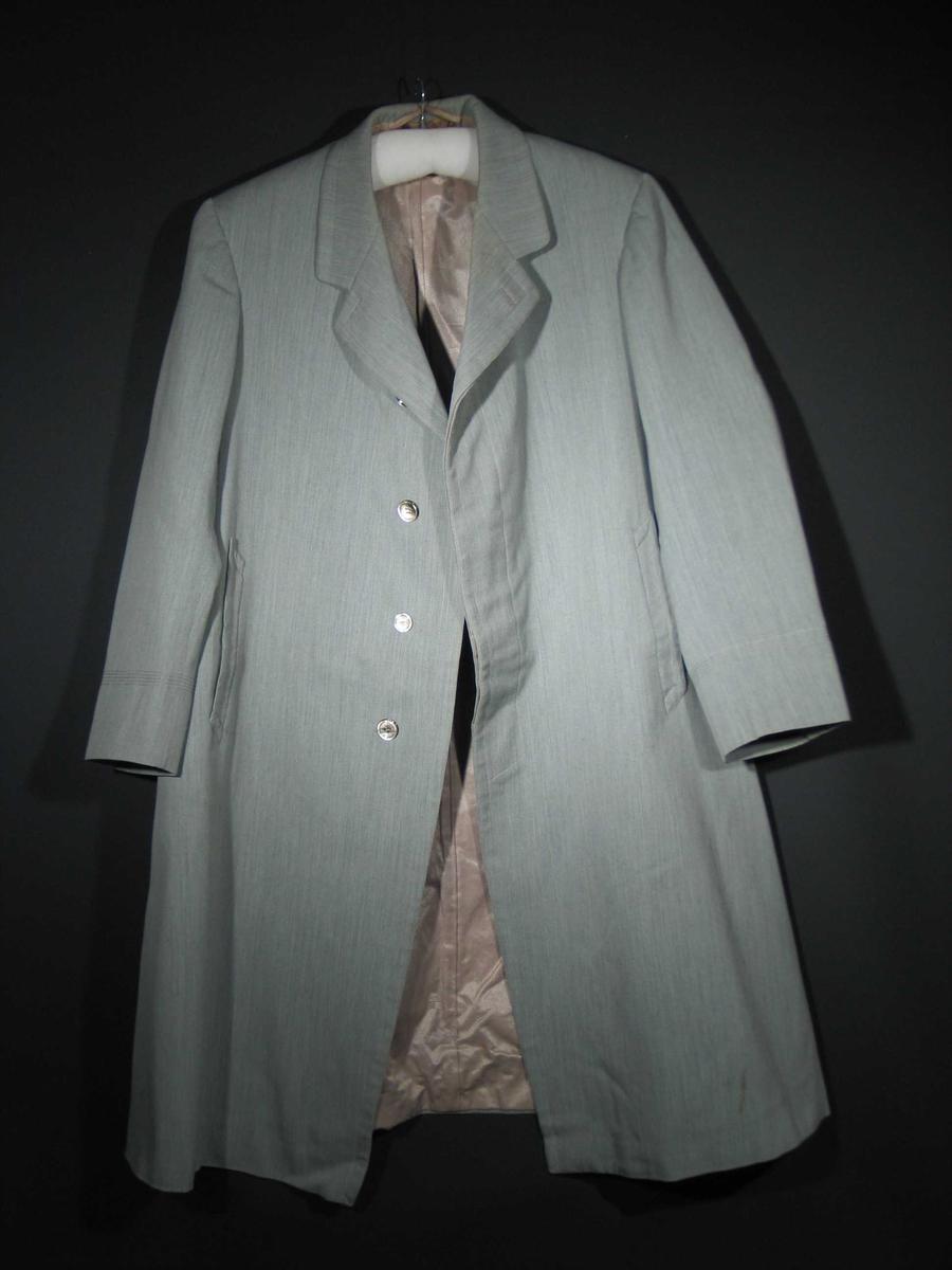 Gråmelert ytterfrakk foret med gråbrunt blankt stoff (blanding av silke og bomull). Den har maskinsydde stikningebord på ermene, to stikklommer og en innerlomme. Lukkes med fire blanke knapper.