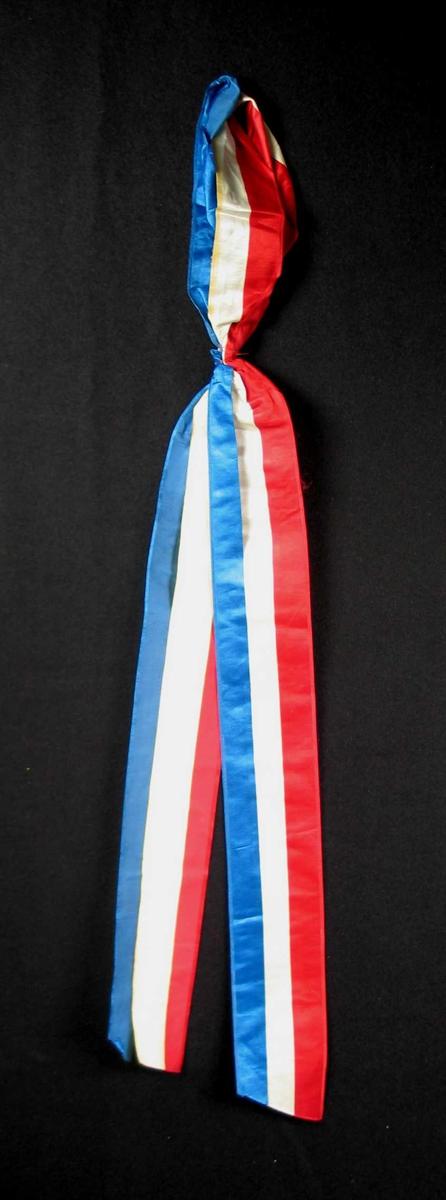 Begravelsessløyfe i rød, blå og hvit silke. Ingen tekst.