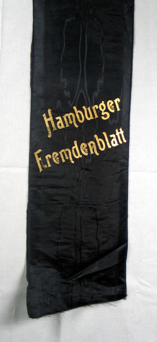 Begravelsessløyfe i svart mønstret silke med tekst i gull.