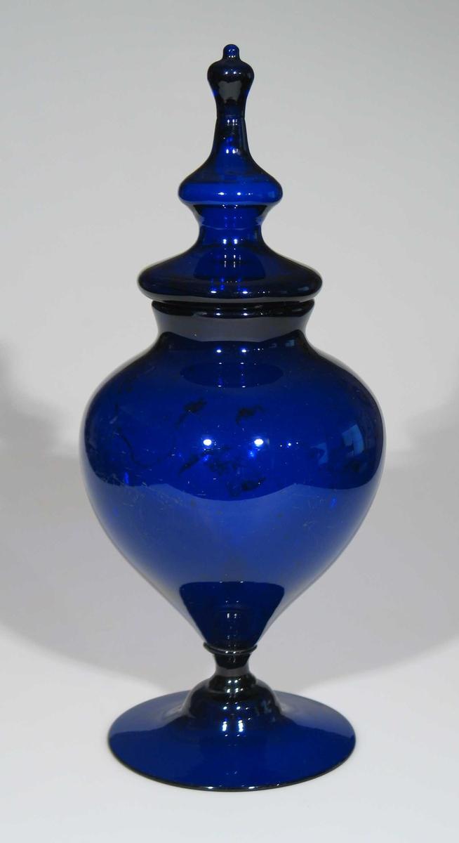 Blå glasskrukke med lokk. Krukken har omvendt pæreform med kort stett.