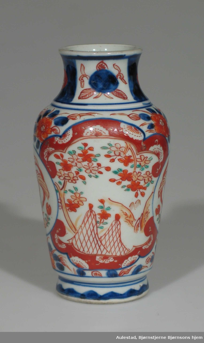 Hvit vase i porselen med dekor i blått og rustrødt. Vasen er urneformet.