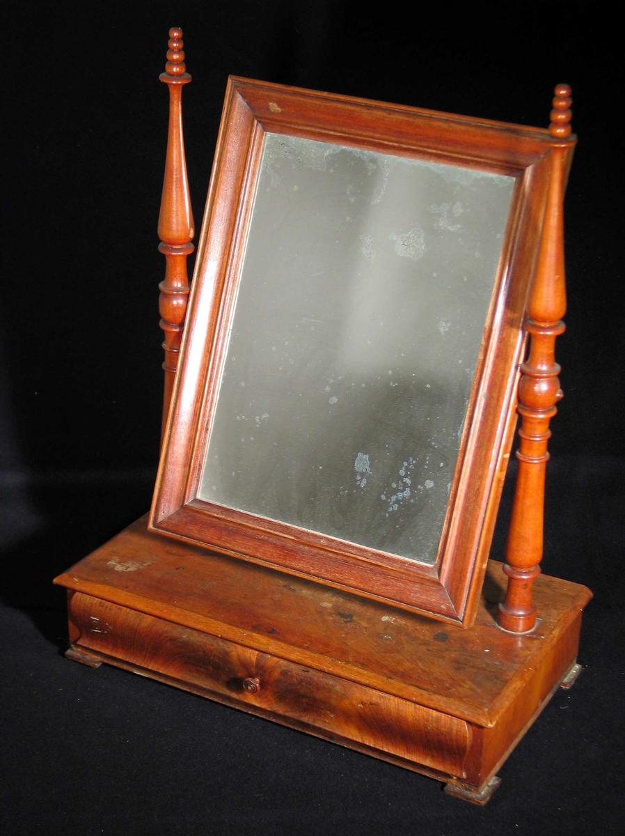 Speil i treramme festet mellom to profilerte staver. Speilet har understell med en buet skuff.