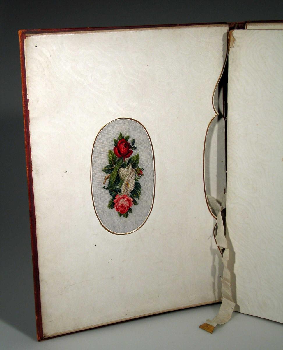 Skrivemappe i burgunder skinn med preget bord. Innvendig i permen et brodert rosemotiv og to lommer med bånd.