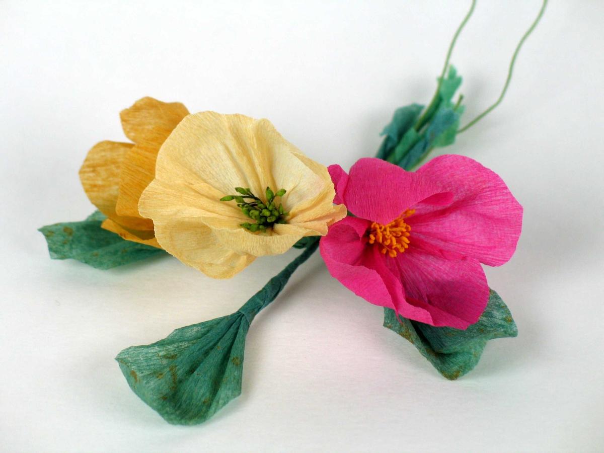 Tre små blomsterbuketter laget i kreppapir. Ligger i en pappeske med innskrift på lokket.