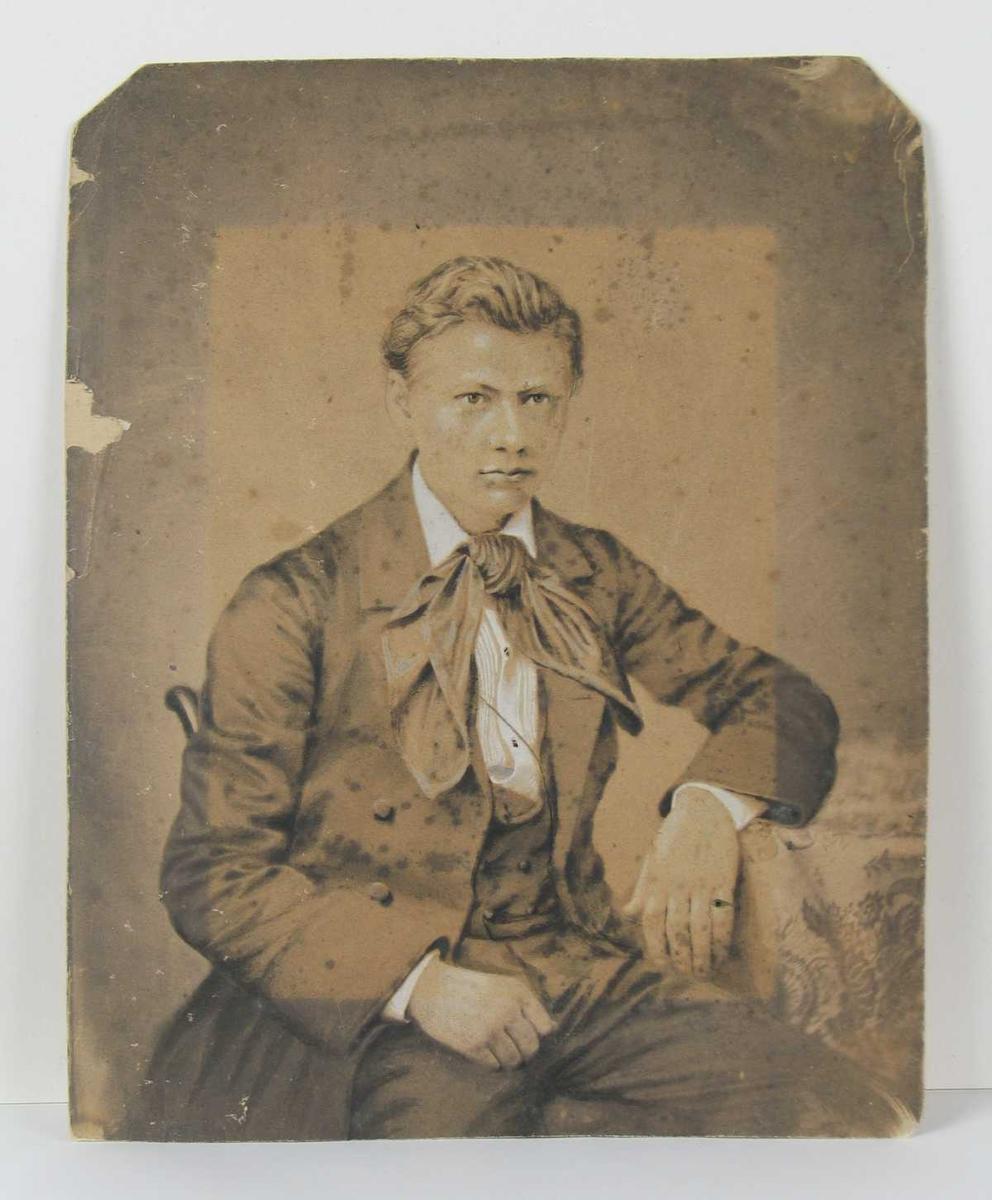 Portrett av en ung mann, fotografert i atelier.