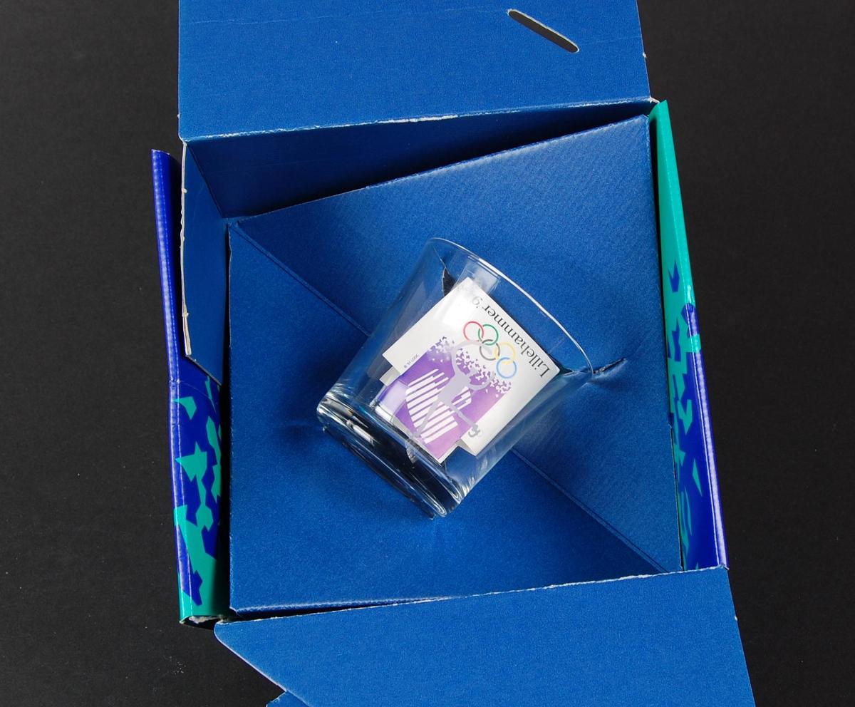 Cocktailglass med piktogram for sportsgrenen kunstløp. Glasset ligger i en blå og grønn pappeske med krystallmønster. Krystallmønsteret inngikk i LOOCs designprogram. På esken er det også en logo for de olympiske vinterleker på Lillehammer i 1994.