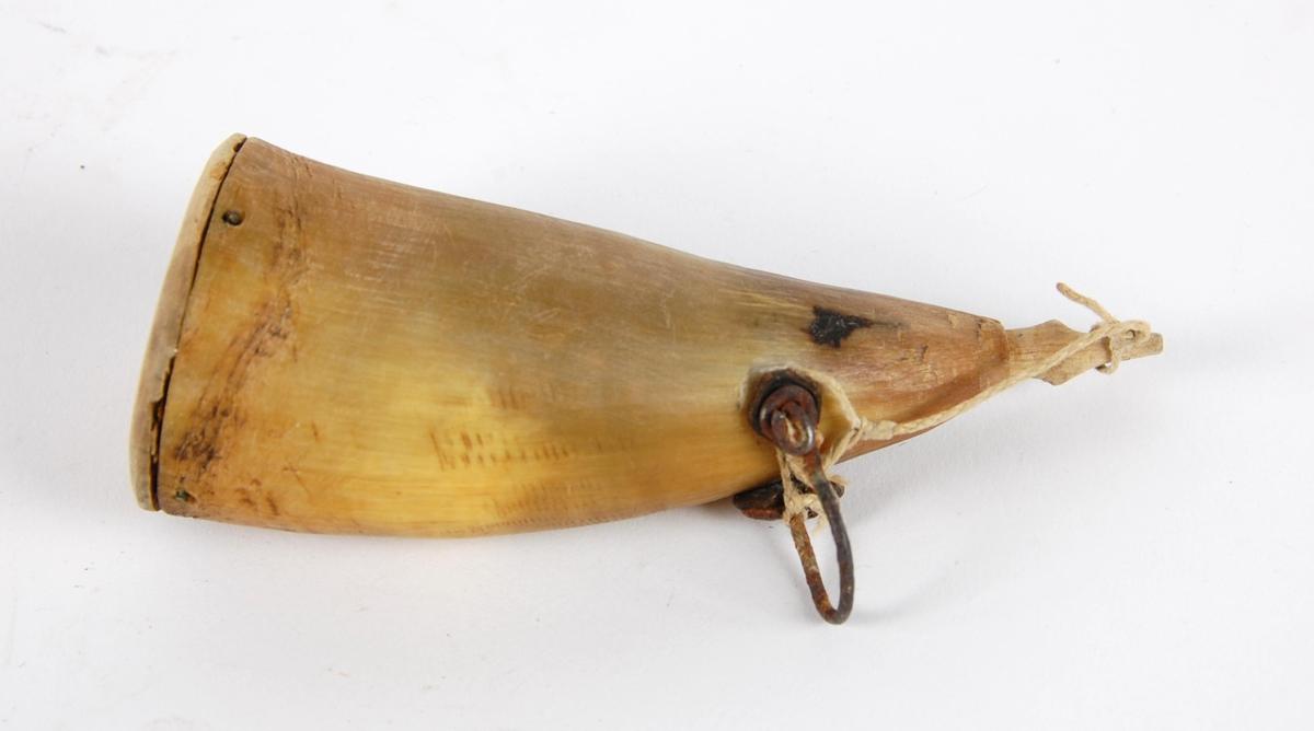 Rundt krutthorn av horn, med bunnstykke av tre.  Jernkrok til oppheng. Trepropp i tuten.
