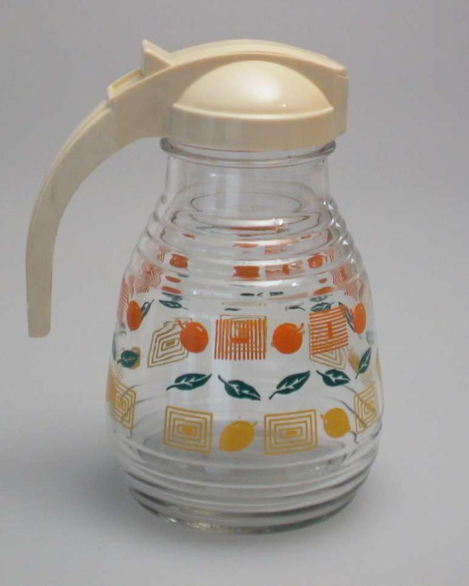 Glassmugge med plasthank og fjærbelastet lukking på lokket. Muggen er dekorert av blader, appelsiner og sitroner.
