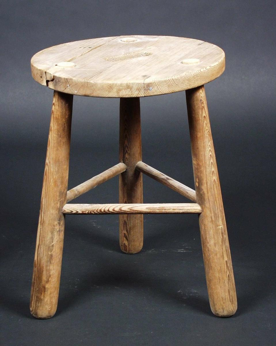 Krakk med rundt sete og tre bein. Beina er innfelt i setet, og setet har hull for bæring.