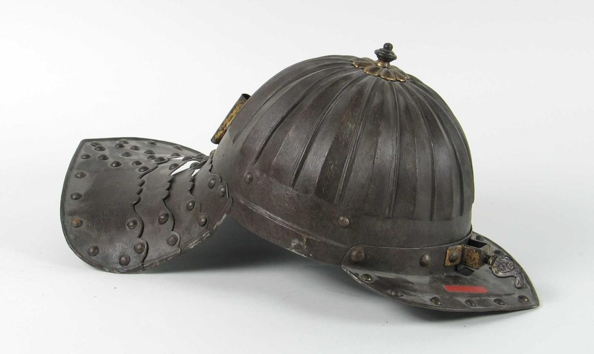 Hjelm smidd av en plate med profilert hjelmbolle Trekantet skygge og bred nakkeskygge konstruert av påklinkede lameller. Forgyllt toppplate, nasalholder og fjærduskholder.