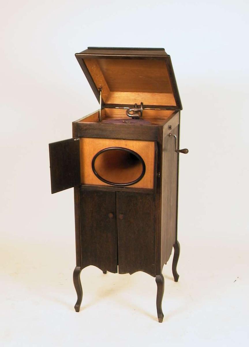 Grammofonkabinett med sveivegrammofon. Under grammofonen er det to sett skapdører, ett for 'høytaler' og ett reelt skap. Kabinettet er brunbeiset. Sveiven på siden av kabinettet er løs.