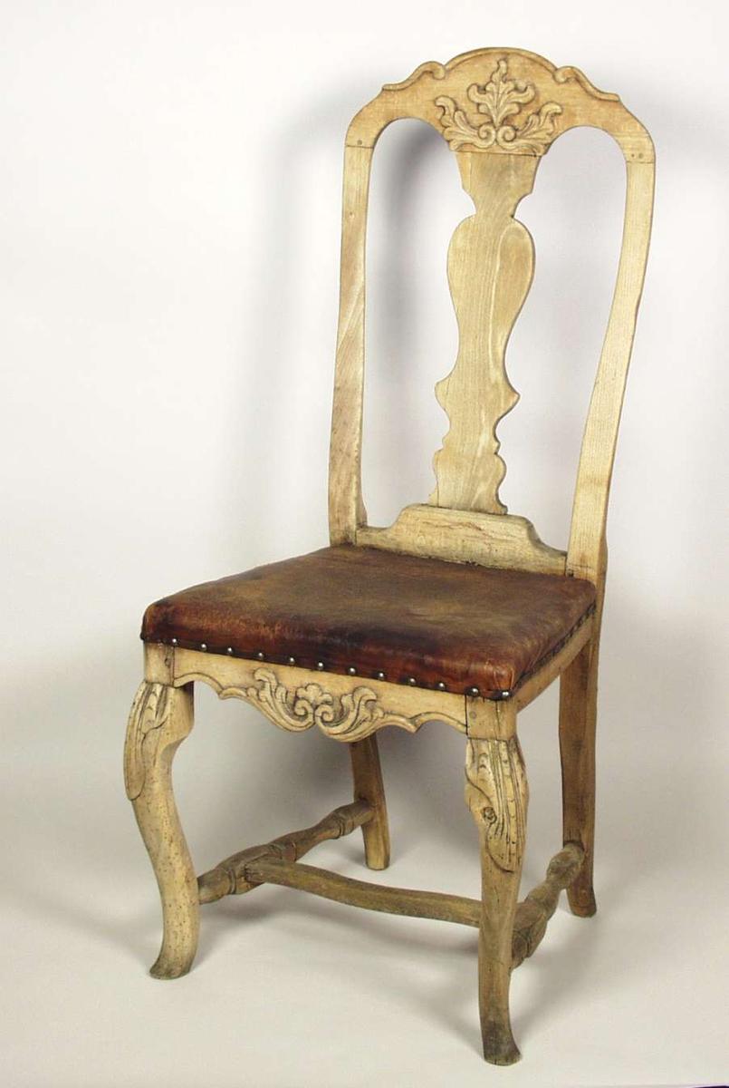 Høyrygget stol med polstring dekket av lær. Stolen er lutet. Stolen har svungne forben med skjell på knærne. Sidesprossene er dreide. Stolen har utskåret, symmetrisk bladverk på sarg og toppstykke.