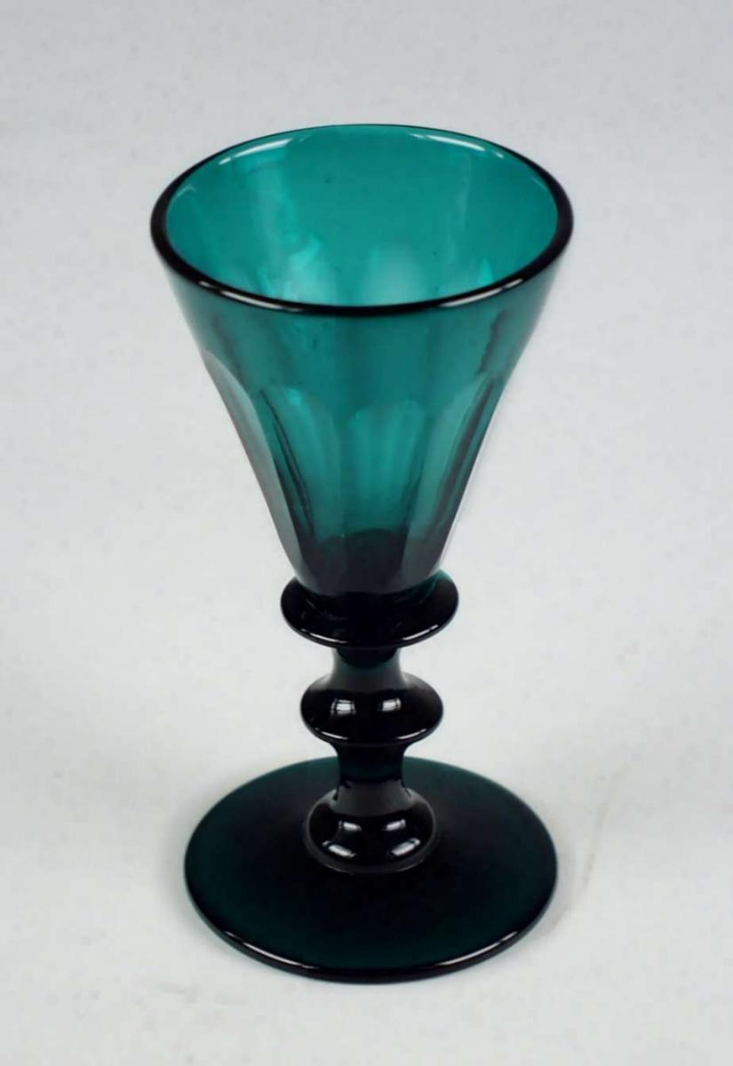 Mørk grønt vinglass med spiss, fasettslipt klokke og skive i stetten.