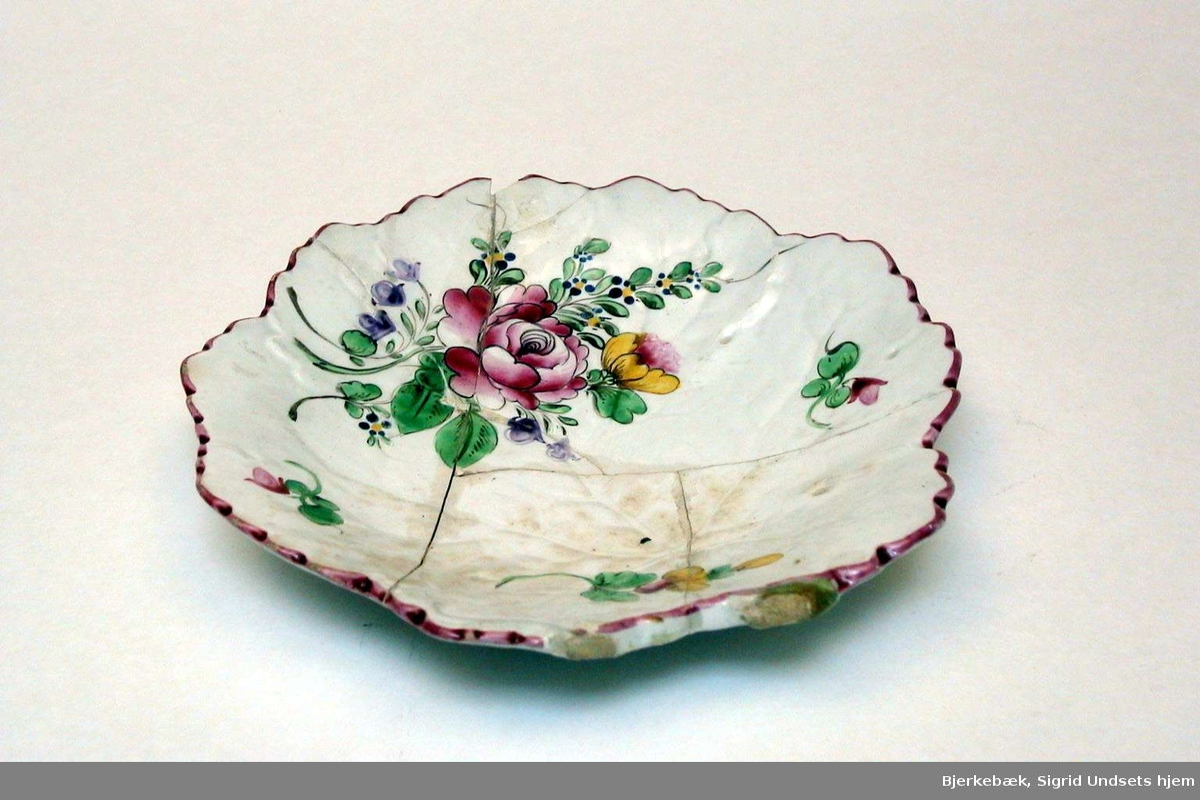 Konfektskål i keramikk med kremfarget glasur og med blomsterdekor. Skålen er formet som et blad. Det er slått biter av den, og skålen er limt flere steder.