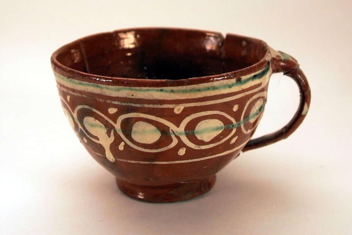Grovt laget kopp i brunt leirgods med 'meksikansk' dekor. Koppen er limt.