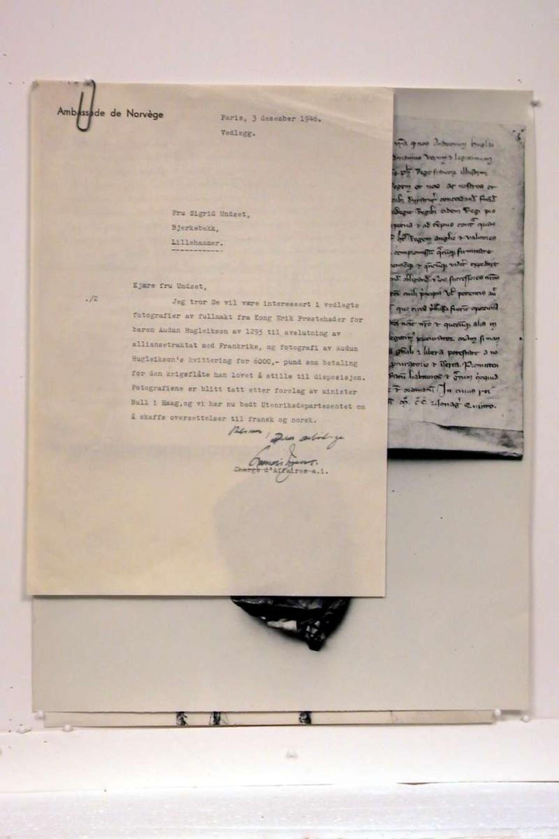 Pappomslag som inneholder 2 sort/hvite fotografier av historiske tekster og et brev.