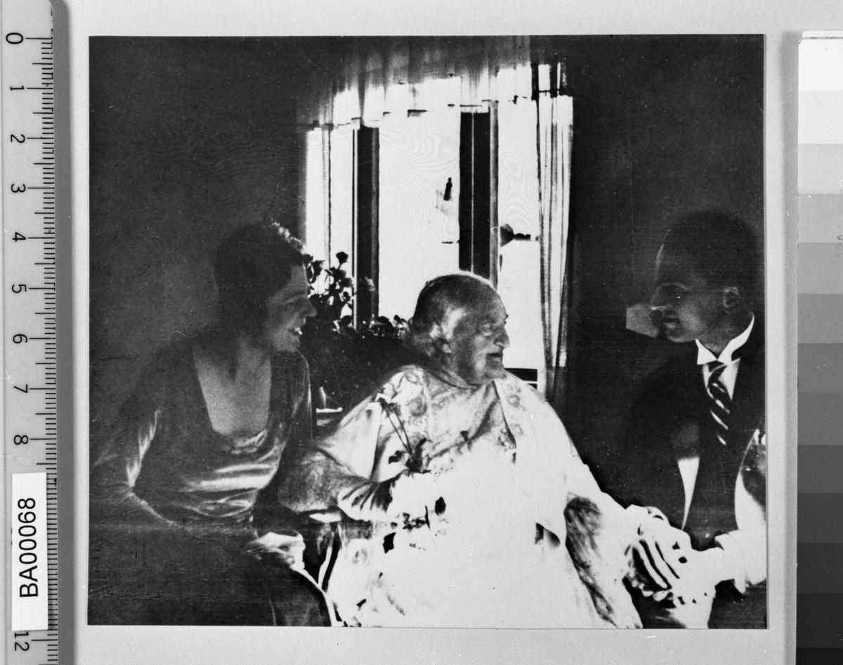 Bryllupsbilde med gammel dame sittende imellom brud og brudgom i stue. Den gamle damen ser på brudgommen, et barnebarn.