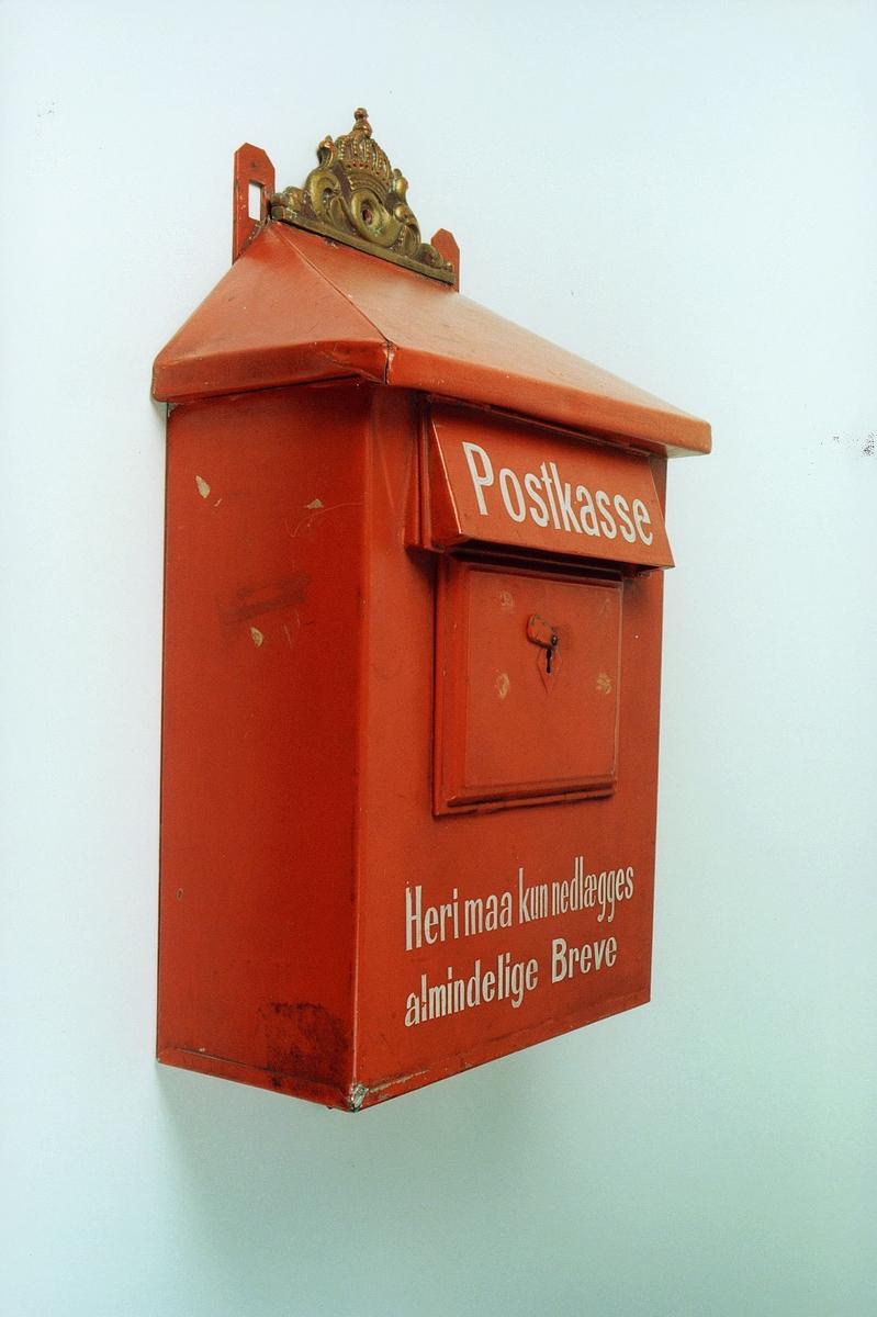 """Postmuseet, gjenstander, postkasse, støpt posthorn og krone øverst på kassen, """"Heri maa kun nedlægges almindelige Breve"""", høyre side."""