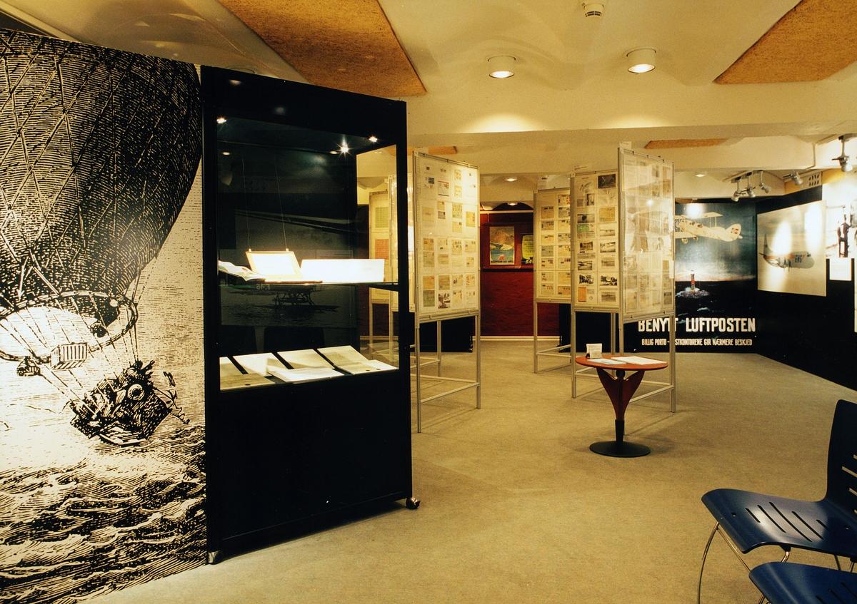 """Postmuseet, utstilling, """"Luftpost i Norge - fra ballong til jet"""", bilde av luftballongen med kurv, monter, rammer med eksponater, luftpostplakater."""