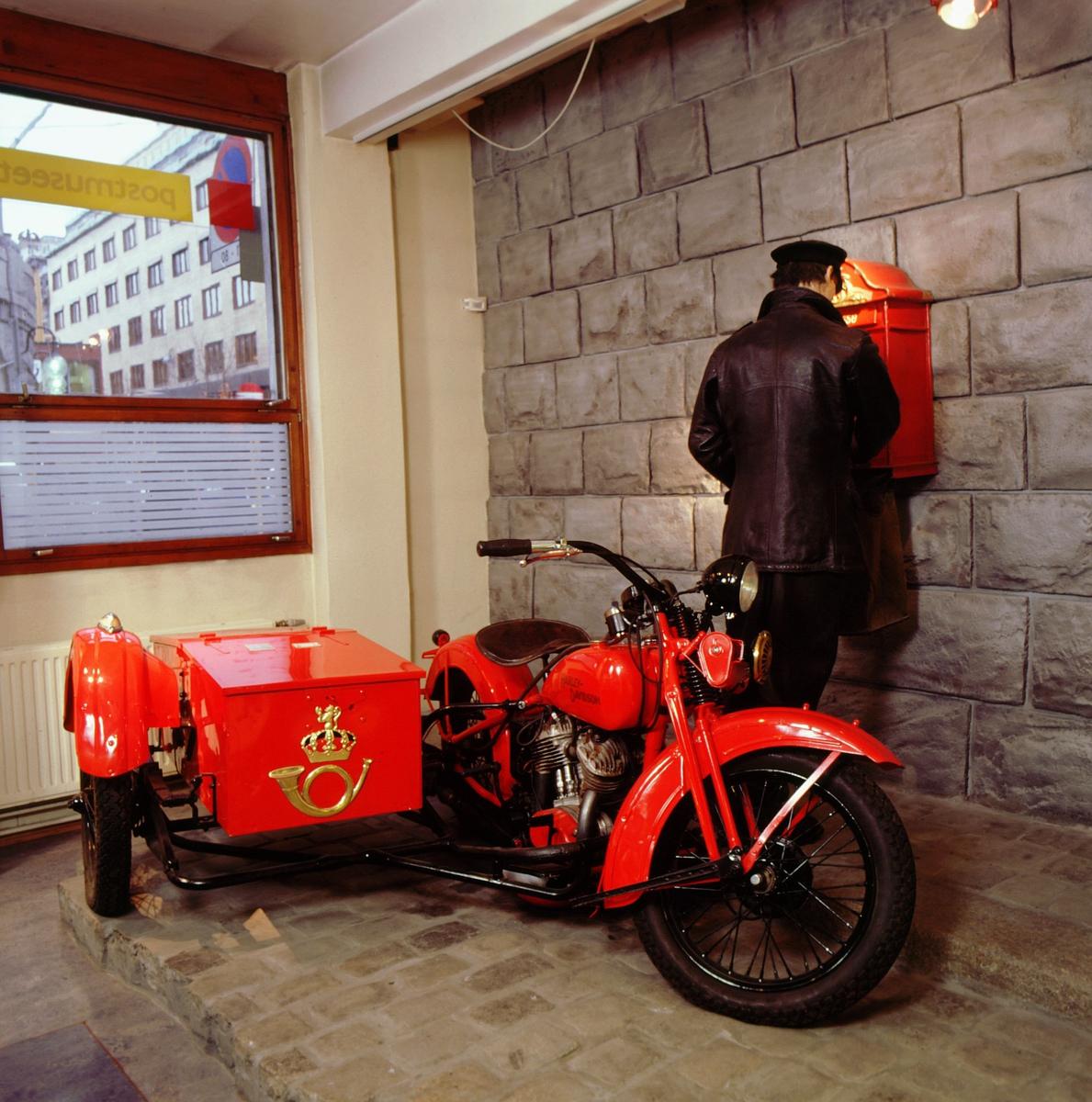 postmuseet, utstilling, transport, motorsykkel, Harley Davidson med sidevogn og postlogo i gull, postbud i skinnjakke tømmer postkassen