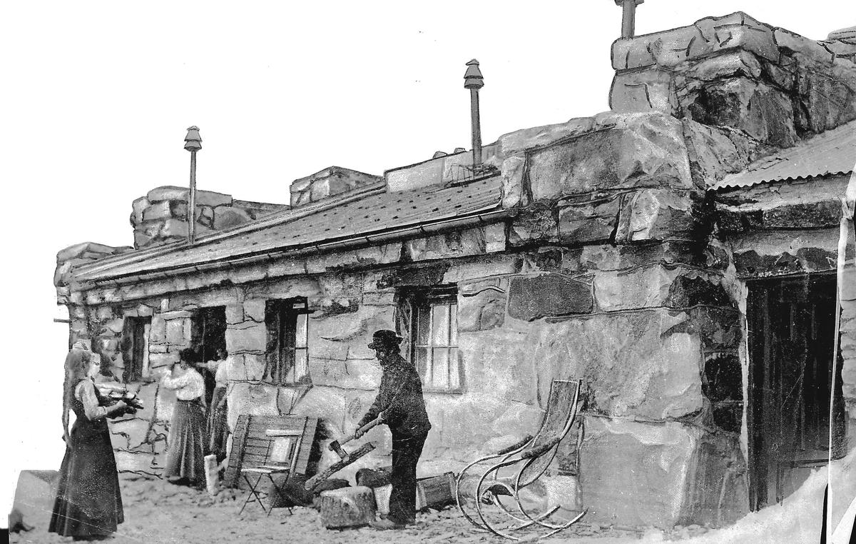 """""""Tong""""  steinbygning med tre personer utenfor"""