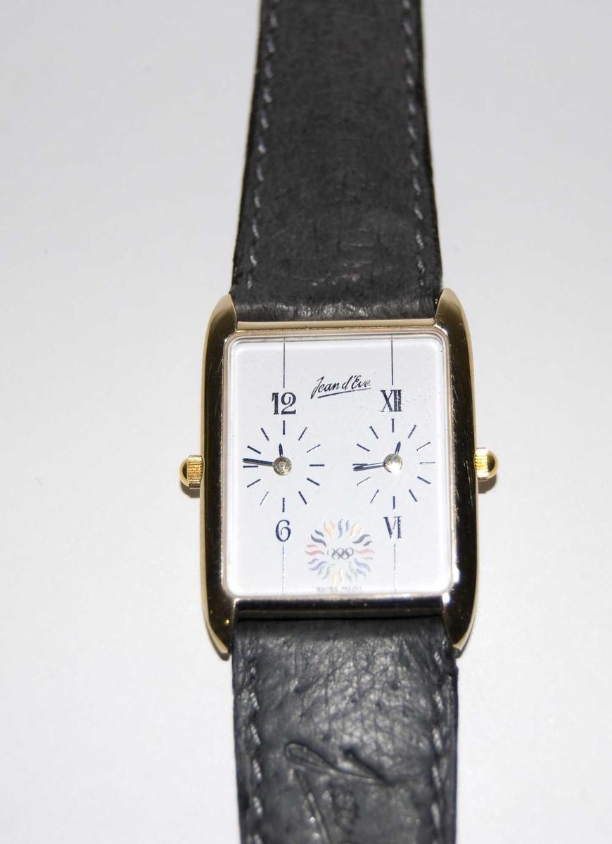Gull- og sølvfarget armbåndsur med sort reim og hvit urskive. På urskiven er det et emblem med motiv av de olympiske ringene og en stilisert sol. Det følger med et grått etui.