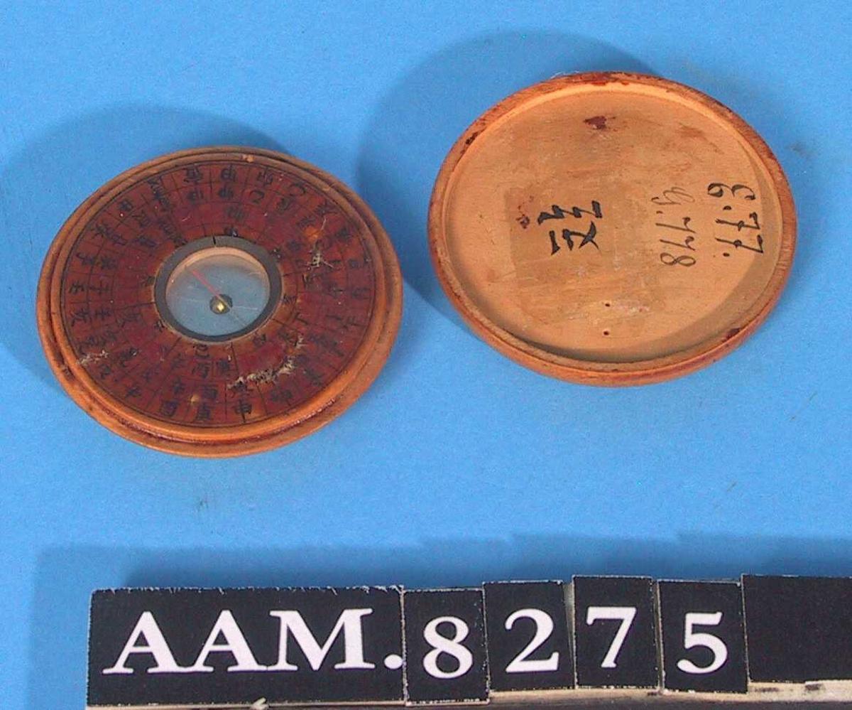 Tre. Av form som en   flat, rund  dåse med lokk, selve kompasset har diam. 2 cm., rundt dette  fire  rader tunget sort kontur. Sorte og røde skrifttegn og  Gml. nr. .