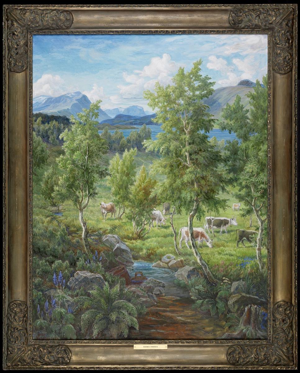 Landskap, bekk m. blomster v. bredden, saftig grønt gress, bjerketrær, kyr, i bakgr. blått vann og blå fjell, blå og grå himmel