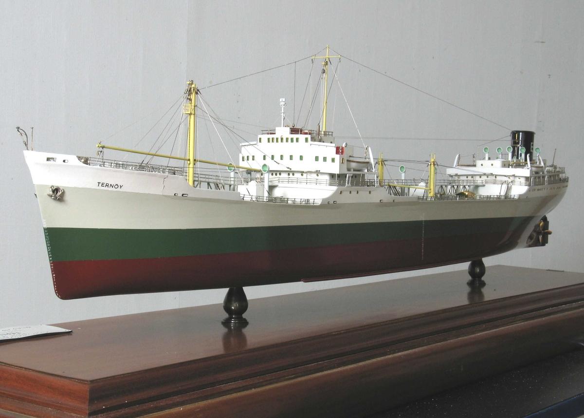 """Skipsmodell, profesjonelt utført, montert på mahognyplate i glassmonter. Tankskipet  Ternøy"""", tilhørende Olaf Boes rederi, Arendal. Skroget malt lysgrått, grønt med rødbrun kjøl. På sort skorstein en hvit B."""
